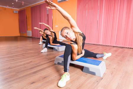 gimnasia aerobica: Vista frontal de tres mujeres jóvenes que estiran las piernas y brazos en la posición Sentado en Paso Plataformas en el paso aeróbico Clase de colorido Dance Studio con Suelo de madera