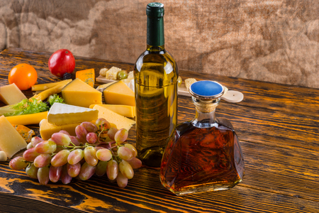 unlabelled: Bottle of White Wine and Amber Whiskey Alcohol on Rustic Wooden Table with Variety of Gourmet Cheese and Grapes - Ingredients for Cheese Board Stock Photo