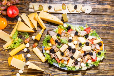 carnes y verduras: Vista elevada de ensalada gourmet elaborados con verduras frescas, moras, variedad de quesos y carnes con tabla de quesos e ingredientes de mesa de madera rústica