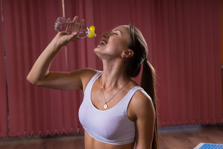 muscle girl: Half Body Shot of a Happy Healthy Woman Drinking Water in a Bottle with Eyes Closed.