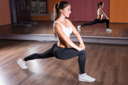 Full Length Profile View of Young Brunette Woman Wearing Exercise Clothing and Stretching in Leg Lunge Position with Straight Back in Dance Studio in front of Mirrors Stock Photo