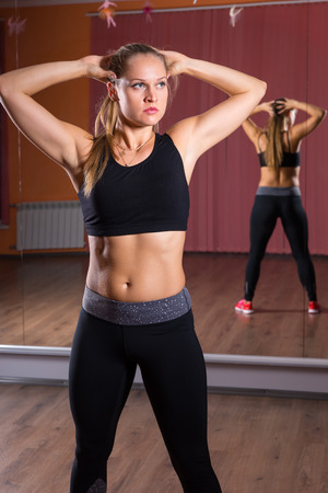 mirrored: Three Quarter Length Portrait of Young Blond Female Dancer Wearing Exercise Clothing Standing in Dance Studio with Hands Behind Head and Reflection in Mirrored Wall