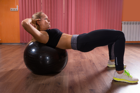 Young woman practicing pilates in a gym balancing on her back across the ball to strengthen and tone her muscles, side view in a health and fitness concept