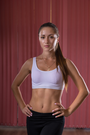 body curve: Portrait of an Athletic Young Woman with Hands Holding Waist and Looking at the Camera.