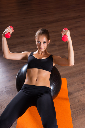 pilates ball: Young woman practising pilates balancing on her back over a pilates ball raising a dumbbell in each hand with a look of concentration Stock Photo