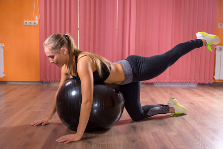 renforcer: Woman working out with a pilates ball balancing across it with her leg raised to strengthen and tone her muscles, healthy lifestyle concept