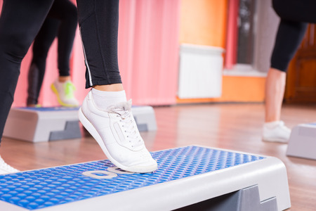 DAnce background: Close Up of Woman Wearing White Sneakers Doing Toe Tap on Step Platform in Aerobic Exercise Class with Group of Women in Background in Dance Studio