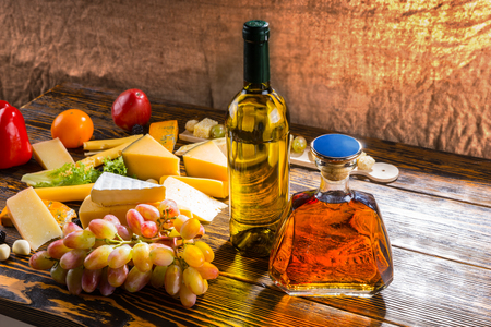 unlabelled: Appetizers at a party with a large assortment of speciality cheeses, fresh grapes, bottle of wine and whiskey decanter on a wooden table