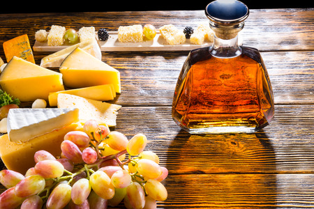 cheese platter: Whiskey or brandy in a modern stylish decanter on a buffet table with assorted cheeses on a platter and bunch of fresh grapes Stock Photo