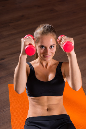 hand weights: Portrait of Smiling Young Blond Woman Doing Ab Crunches with Hand Weights on Bright Orange Floor Mat and Looking at Camera in Exercise Studio Stock Photo