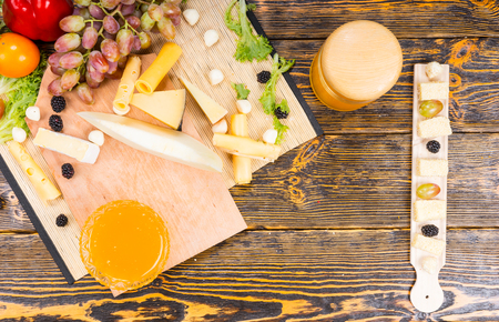sumptuous: Overhead view of a cheese platter on a buffet with an assortment of gourmet cheeses, fresh grapes and a bowl of dipping honey on a wooden table