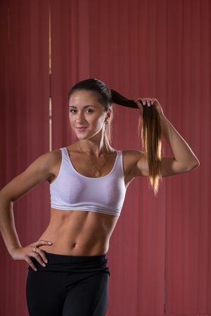 Three Quarter Shot of a Pretty Athletic Young Woman in Fitness Outfit, Holding her Long Hair and Smiling at the Camera.
