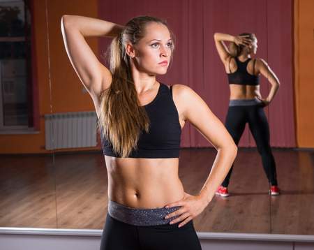 limbering: Waist Up Portrait of Serious Young Blond Woman Wearing Exercise Clothing and Standing with Hand on Hip in front of Mirrored Wall - Woman Stretching Arm in Studio