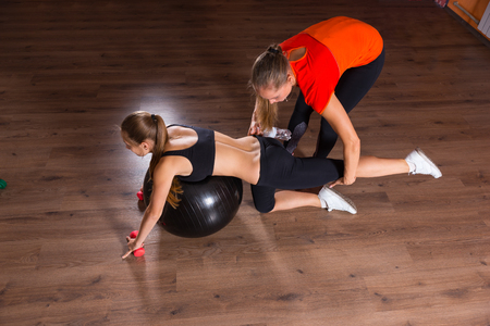 cardiovascular exercising: High Angle Full Length View of Personal Trainer Assisting Young Woman with Posture on Inflatable Exercise Ball in Studio with Hardwood Floors