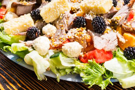 carnes y verduras: Cerca de ensalada gourmet elaborados con frutas y hortalizas frescas, variedad de quesos y embutidos en la mesa de madera rústica