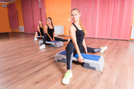 cardiovascular exercising: Front View of Three Young Women Stretching Legs in Seated Position on Step Platforms in Step Aerobic Class in Colorful Dance Studio with Hardwood Floor