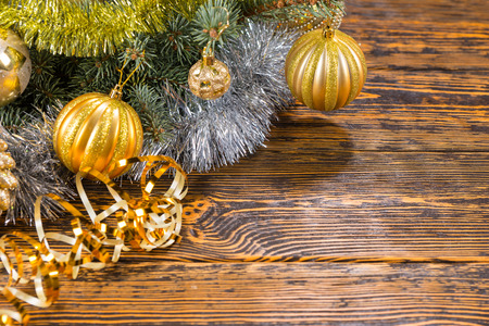 golden ball: Rustic Christmas bauble background with golden balls on a fir branch over a rustic wood background with gold tinsel and copyspace for your Xmas greeting