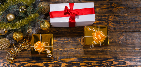 giftwrapped: High Angle Panoramic View of Christmas Gifts on Rustic Wooden Table Beside Evergreen Pine Boughs Decorated with Gold Balls and Tinsel Garland - Festive Still Life with Copy Space