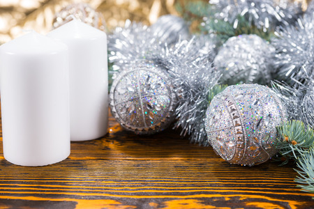 themed: Silver themed Christmas with an arrangement of decorative patterned baubles and tinsel alongside two white candles on a textured wood background