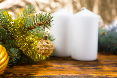 unlit: Festive Still Life of Evergreen Branches Decorated with Gold Balls and Tinsel Garland on Rustic Wooden Table with Two White Unlit Pillar Candles with Copy Space in Foreground