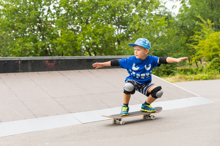 safety gear: Young boy in a trendy blue outfit and safety gear practicing his skateboarding balancing on his board with outstretched arms Stock Photo