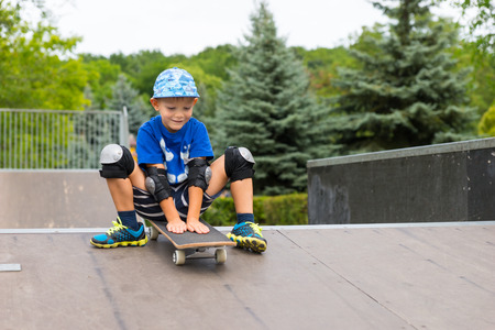 knee pads: Full Length Front View of Young Boy Wearing Elbow and Knee Pads Sitting on Skateboard at Top of Ramp Looking Excited with Anticipation and About to Ride Down in Seated Position in Skate Park