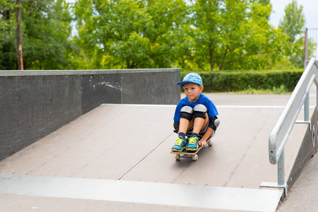 elbow pads: Front View of Young Boy Wearing Safety Pads Sitting on Skateboard and Riding Down Ramp in Skate Park Surrounded by Green Trees
