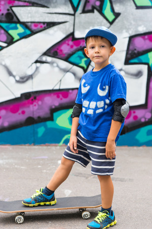 boy skater: Full Length Portrait of Young Boy Standing with One Foot on Skateboard in front of Graffiti Covered Wall in Skate Park and Looking at Camera with Neutral Expression