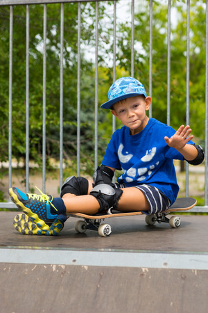 skate park: Full Length Portrait of Young Boy with Silly Facial Expression Making Hand Gesture and Sitting on Skateboard on Top of Ramp in Skate Park
