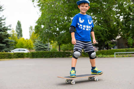 jaunty: Handsome sporty young skateboarder balancing on his skateboard in a trendy blue outfit, smiling at the camera
