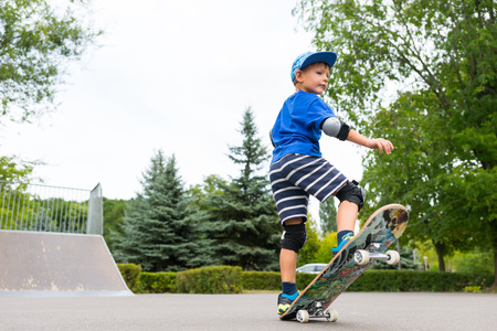 preteen boys: Cute trendy little boy on his skateboard balancing with the front raised in the air as he shows off his skills at the skate park