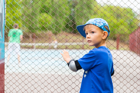 quizzical: Small boy watching a game of tennis standing at the perimeter wire mesh fence turning to look back over his shoulder with a quizzical expression