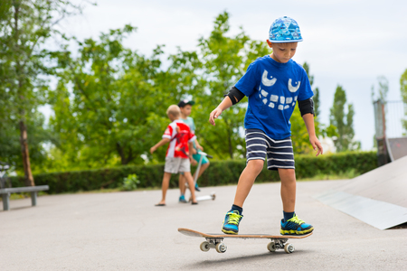 jaunty: Young boy at the skate park playing with his skateboard practicing his moves as other children play in the background