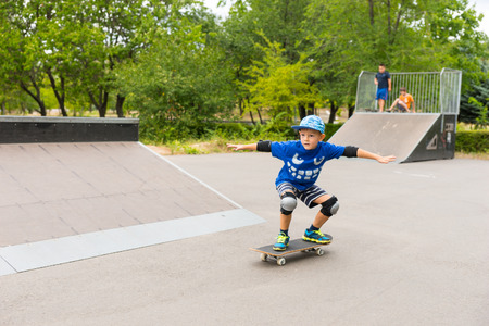 boy skater: Little boy enjoying his skateboard at the park practicing a stylish stance with outspread arms on a sunny summer day