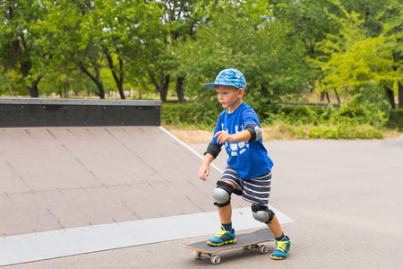 elbow pads: Young boy playing at a skate park on his skateboard as he practices his balancing in a trendy blue outfit with knee and elbow pads