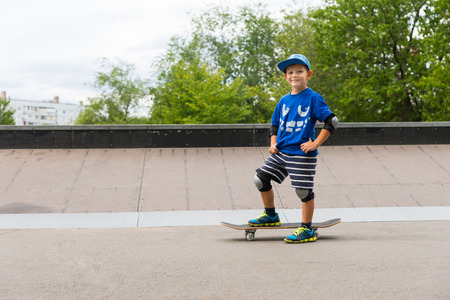 young boys: Confident little boy with a big friendly smile standing with his skateboard on the tarmac at the skate park on a hot summer day, with copyspace Stock Photo