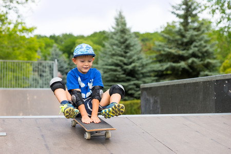 elbow pad: Young boy riding his skateboard down a ramp sitting on it with his feet raised off the ground with a happy smile