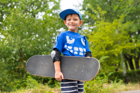 jaunty: Low angle view of a handsome happy proud little boy carrying a skateboard against a background of leafy green bushes Stock Photo
