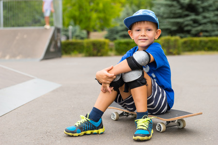 safety gear: Handsome little boy sitting on his skateboard in his safety gear smiling at the camera as he takes a break at the skate park Stock Photo