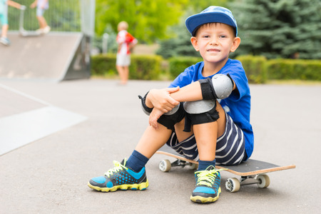 knee pads: Full Length Portrait of Smiling Young Boy Wearing Protective Safety Elbow and Knee Pads Sitting on Skateboard in Outdoor Skate Park Stock Photo