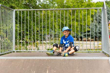 skate park: Smiling Young Confident Boy Sitting on Skateboard at Top of Ramp in Skate Park Surrounded by Green Trees Stock Photo