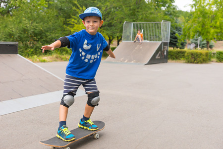 jaunty: Cute small boy skateboarding at a skate park practicing his stance on the board with a happy smile Stock Photo