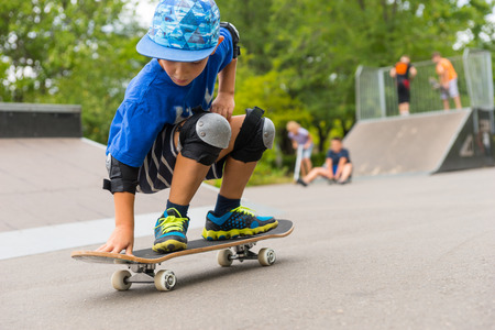 skaters: Full Length Close Up of Young Boy Crouching on Skateboard in Skate Park with Other Skaters in Background on Ramp