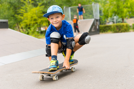 squatting down: Handsome happy little boy on his skateboard squatting down and balancing on the board as he smiles happily at the camera