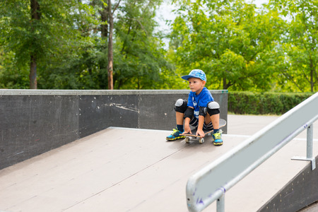 skate park: Young Boy Sitting on Skateboard at Top of Ramp About to Ride Down in Skate Park Surrounded by Green Trees Stock Photo