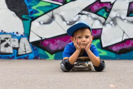 decepcionado: Close Up Retrato de muchacho joven vistiendo gorra de béisbol miente en el estómago en el patín con la cabeza descansando en las manos y mirando a la cámara Decepcionado delante de pared de la pintada Cubierto de Skate Park