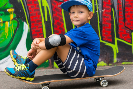 hugging knees: Full Length of Young Boy Wearing Baseball Cap Sitting on Skateboard and Hugging Knees Outdoors in front of Graffiti Covered Wall in Outdoors Skate Park