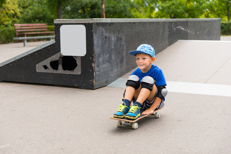 off ramp: Full Length of Happy Young Boy Riding on Skateboard in Seated Position, Coming Off End of Ramp Slope in Skate Park Looking Excited Stock Photo