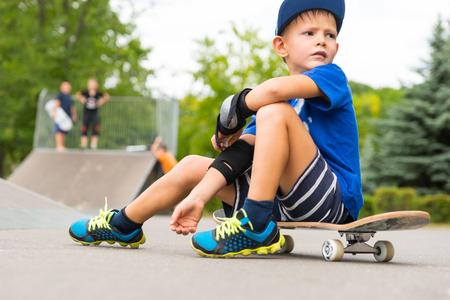 完全な長さで休憩を取って少年のスケート公園 - 少年はスケート ボードの上に座ってと公園のバック グラウンドで他のスケーターとスケートの距離