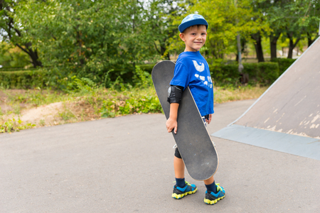 jaunty: Small boy carrying his skateboard at the skate park turning at te bottom of a concrete ramp to smile at the camera
